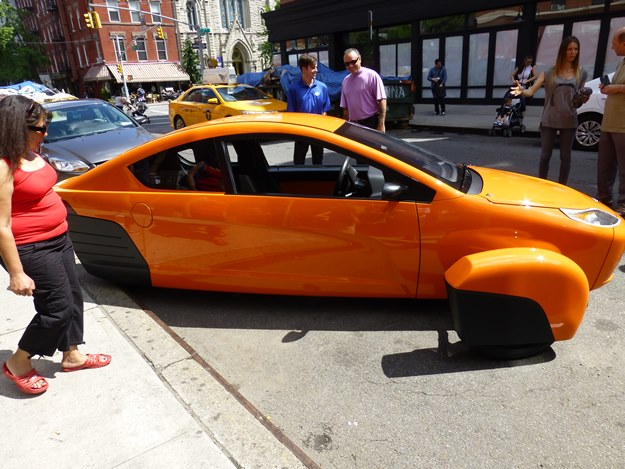 "The Elio in extroverted ""creamsicle"" on Seventh Street in Manhattan. There will be seven production colors, including orange, black, blue, red, silver, white and green.(Jim Motavalli photo)"